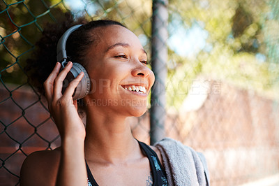 Buy stock photo Shot of a sporty young woman listening to music while standing against a fence outdoors
