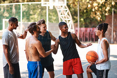 Buy stock photo Shot of a group of sporty young men greeting each other on a basketball court