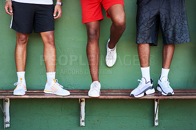 Buy stock photo Closeup shot of a group of sporty men standing on a bench against a wall
