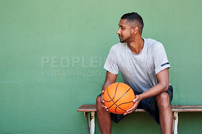 Buy stock photo Shot of a sporty young man holding a basketball while sitting on a bench against a wall
