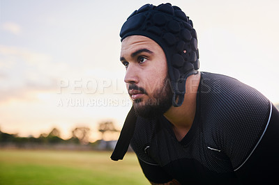 Buy stock photo Cropped shot of a handsome young sportsman wearing headgear and crouching alone during rugby practice during the day