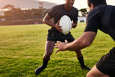 Buy stock photo Cropped shot of two handsome sportsmen playing rugby during a training session during the day