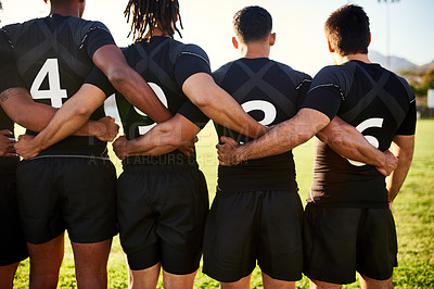 Buy stock photo Cropped shot of a unrecognizable group of sportsmen standing together with their arms around each other before playing rugby
