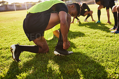 Buy stock photo Cropped shot of a handsome young sportsman tying his shoelaces before playing rugby during the day