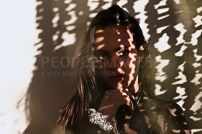 Buy stock photo Cropped portrait of an attractive young woman posing alone against a wall with a shadow cast on her face