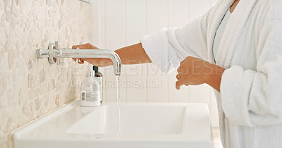 Buy stock photo Cropped shot of an unrecognizable woman running tap water in her bathroom at home