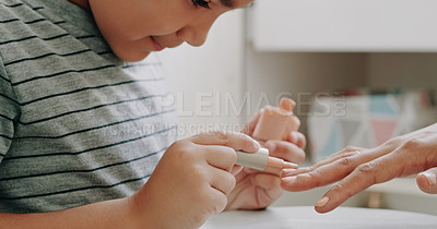 Buy stock photo Cropped shot of an adorable little boy painting his mother's nails at home