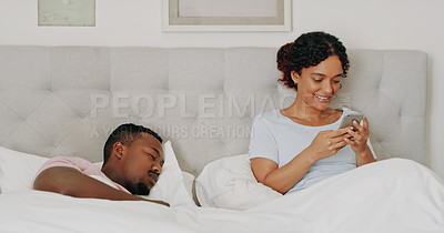 Buy stock photo Cropped shot of an attractive young woman using her cellphone while her husband sleeps alongside her in their bedroom