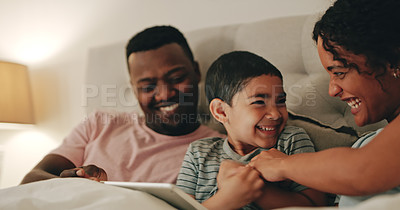 Buy stock photo Cropped shot of a happy young family of three sitting in bed and using a digital tablet together at home
