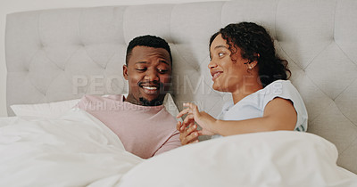 Buy stock photo Cropped shot of a happy young couple bonding and relaxing together in bed at home