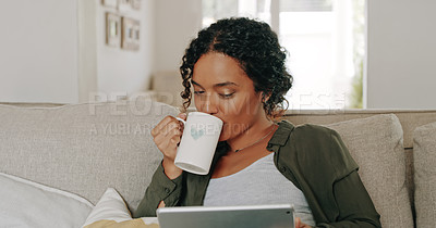 Buy stock photo Cropped shot of an attractive young woman drinking coffee and using her digital tablet at home
