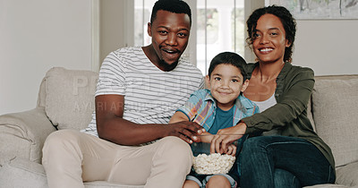Buy stock photo Cropped shot of a happy young family of three eating popcorn and watching movies together at home