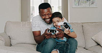 Buy stock photo Shot of a happy father and son playing video games and spending time together at home