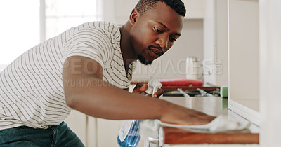 Buy stock photo Cropped shot of a handsome young man cleaning the  counter inside his kitchen at home