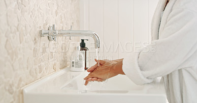 Buy stock photo Cropped shot of an unrecognizable woman washing her hands in her bathroom at home