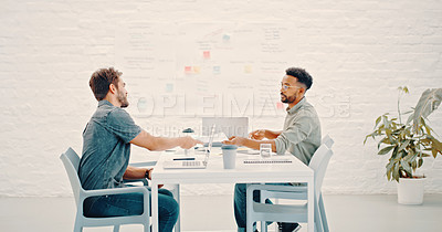 Buy stock photo Shot of two young businessmen working on a project together in a modern office