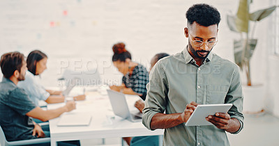 Buy stock photo Shot of a young businessman using a digital tablet while his colleagues have a meeting in the background