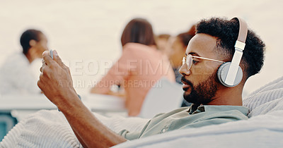 Buy stock photo Shot of a young businessman using a digital tablet and headphones while relaxing on a beanbag in a modern office