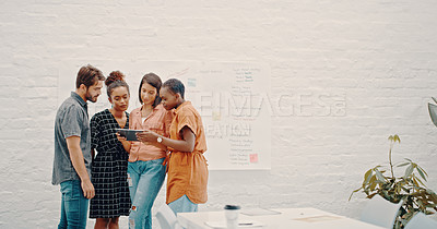 Buy stock photo Cropped shot of a group of designers discussing something on a digital tablet