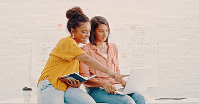 Buy stock photo Shot of two young designers discussing something on a laptop