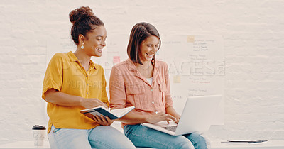 Buy stock photo Shot of two young designers using a laptop while having a discussion in the office