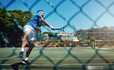 Buy stock photo Full length shot of a handsome young sportsman playing tennis alone on a court during the day