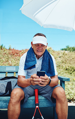 Buy stock photo Cropped shot of a handsome mature sportsman sitting alone and using his cellphone after playing tennis