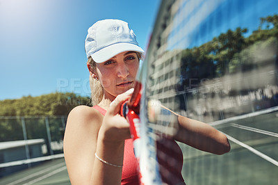 Buy stock photo Cropped portrait of an attractive young sportswoman standing alone and posing on a tennis court during the day