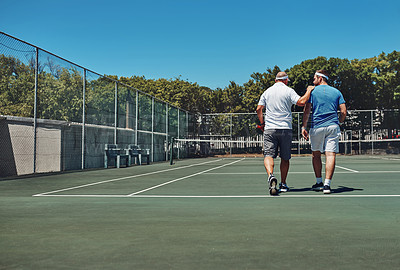 Buy stock photo Full length shot of two unrecognizable sportsmen walking together on a tennis court after a training session