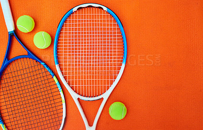 Buy stock photo High angle shot of tennis essentials placed on top of an orange background inside of a studio