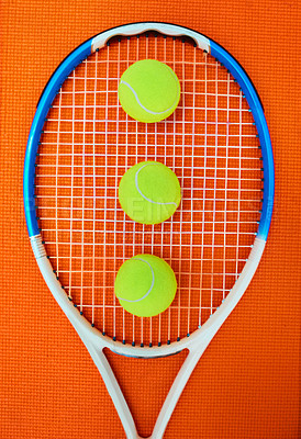 Buy stock photo High angle shot of a single tennis racket and a few tennis balls placed on an orange background inside of a studio