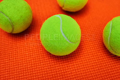 Buy stock photo Closeup of a group of tennis balls placed together on top of an orange background
