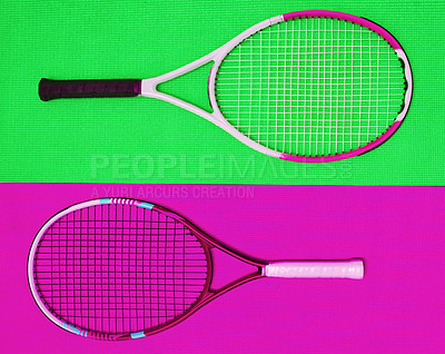 Buy stock photo High angle shot of two tennis rackets placed together on top of a colourful background inside of a studio
