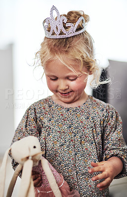 Buy stock photo Cropped shot of an adorable little girl standing alone in the living room and playing with her toys at home