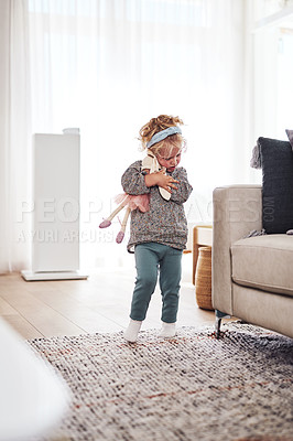 Buy stock photo Full length shot of an adorable little girl standing in the living room and playing with her toys at home