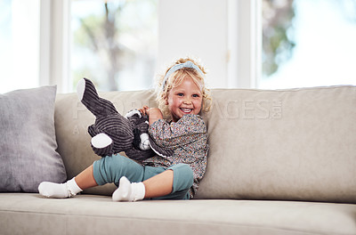 Buy stock photo Full length shot of an adorable little girl sitting alone on the sofa and playing with her toys at home