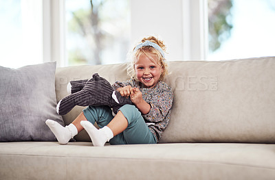 Buy stock photo Full length portrait of an adorable little girl sitting alone on the sofa and playing with her toys at home