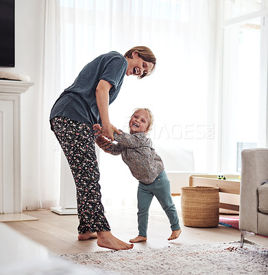 Buy stock photo Full length shot of an attractive young mother and playing with her daughter in the living room at home