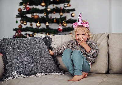 Buy stock photo Full length shot of an adorable little girl sitting alone on the sofa during a day at home