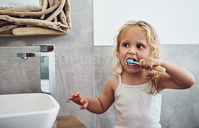 Buy stock photo Cropped shot of an adorable little girl standing alone and brushing her teeth during her morning routine at home