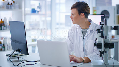 Buy stock photo Shot of a scientist using a laptop and computer in a lab