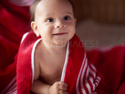 Buy stock photo Cropped shot of an adorable little baby boy wrapped in a red blanket at home