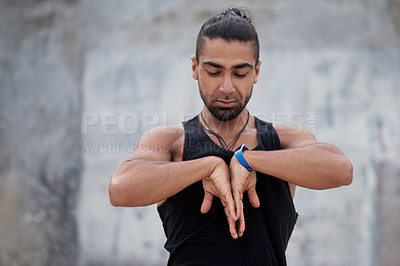Buy stock photo Shot of a handsome young man exercising and practicing yoga outdoors
