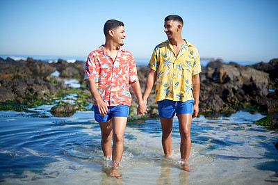 Buy stock photo Full length shot of an affectionate gay couple holding hands while walking through a tidal pool at the beach