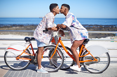 Buy stock photo Full length shot of an affectionate gay couple kissing while riding bicycles along the promenade during a day out