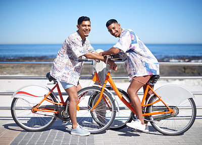 Buy stock photo Full length portrait of a young gay couple bonding together and riding bicycles along the promenade during a day out