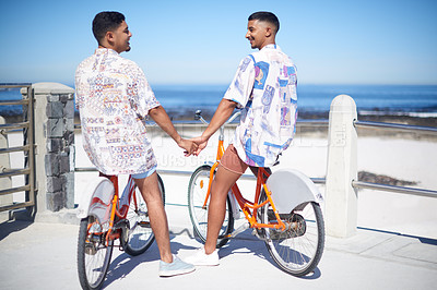 Buy stock photo Full length shot of an affectionate gay couple bonding together and riding bicycles along the promenade during a day out