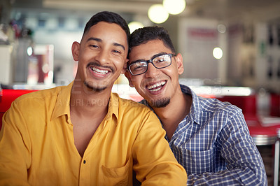 Buy stock photo Cropped portrait of a young gay couple sitting together and bonding during a date in a diner