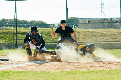 Buy stock photo Full length shot of a young baseball player reaching base during a match on the field