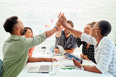 Buy stock photo Shot of a group of businesspeople giving each other a high five during a meeting in an office
